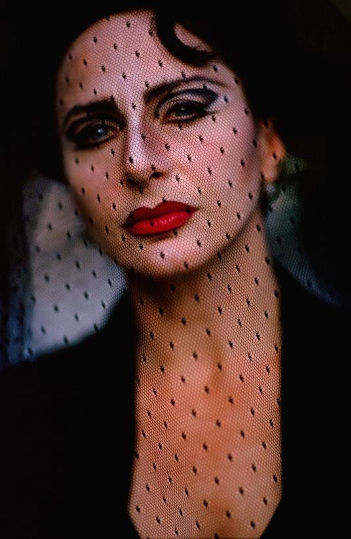 Portrait d'une actrice sicilienne qui regarde l'objectif à travers un voile noir à pois.