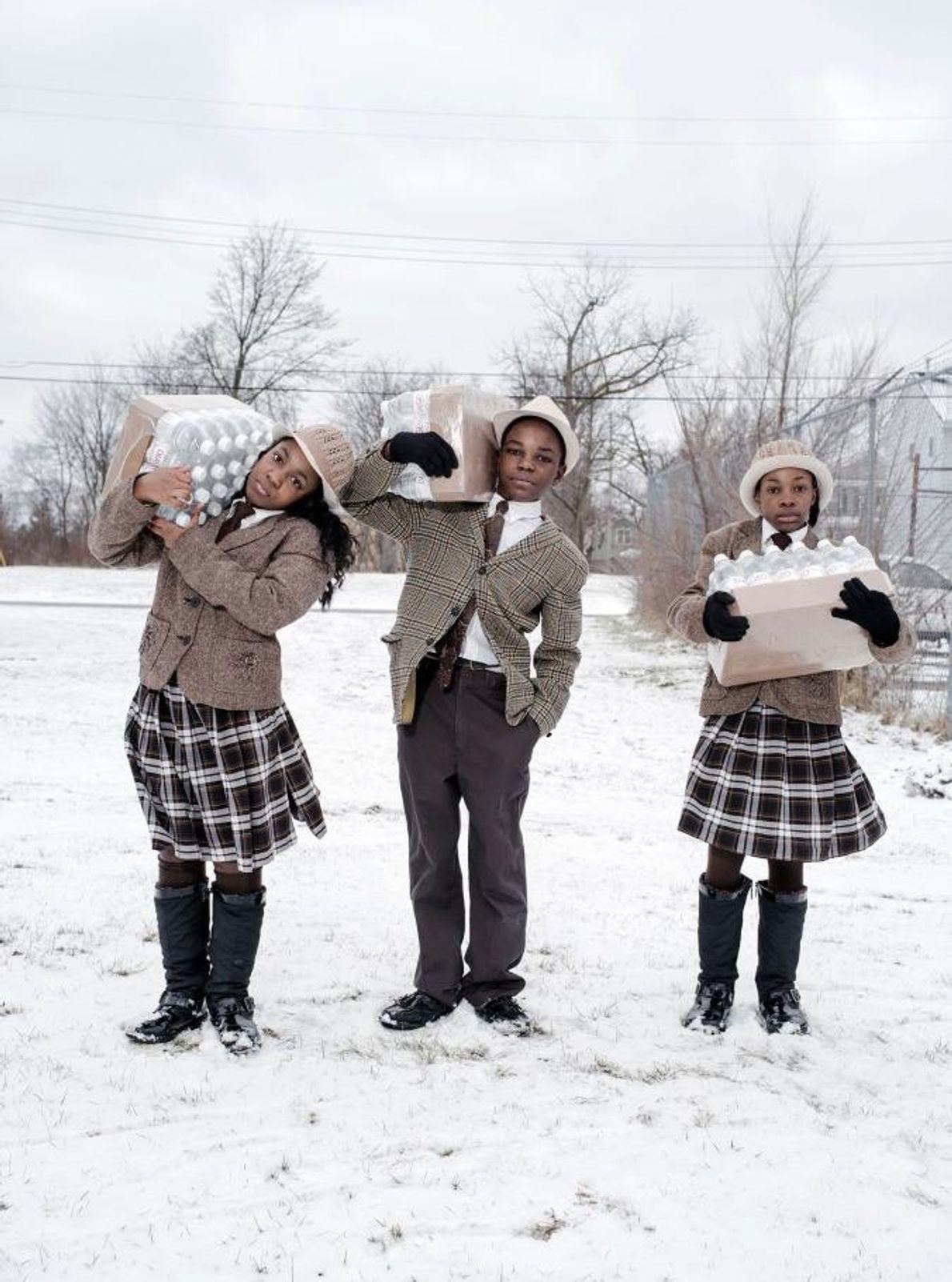 Julie, Antonio et India Abron viennent de récupérer leur allocation journalière de bouteilles d'eau à Flint, ...