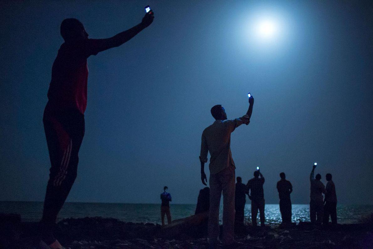 Sur une plage de Djibouti, des Somaliens cherchent du réseau, transmis par le relais téléphonique du ...
