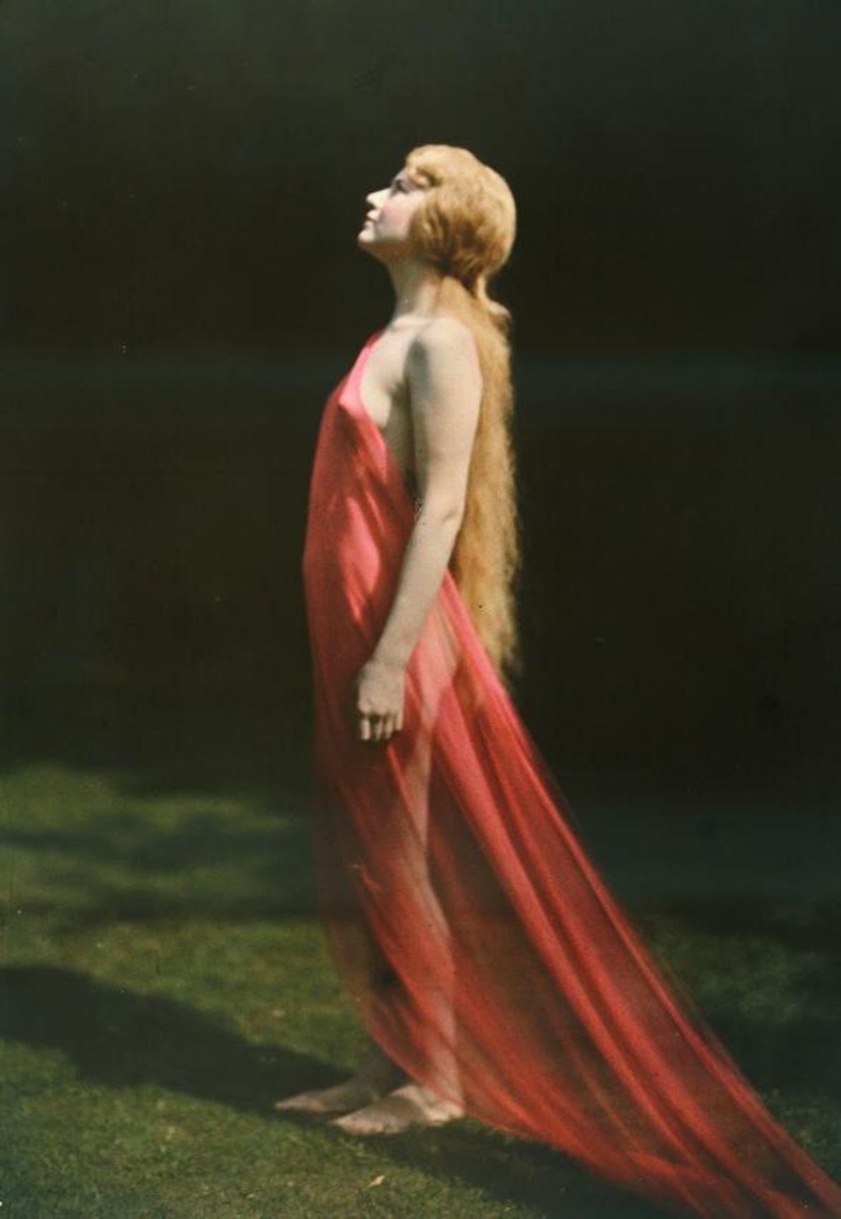 Enveloppée de soie rouge, une femme regarde vers le ciel dans cette photo autochrome. National Geographic ...