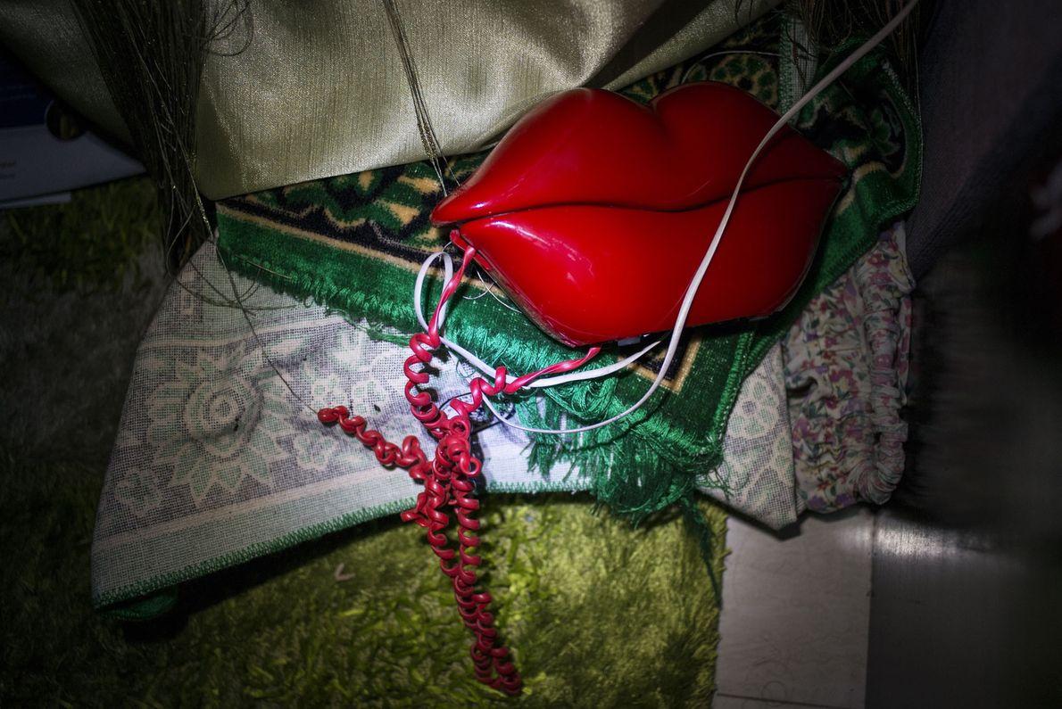 Un téléphone en forme de bouche et un tapis de prière traînent dans le coin d'une ...