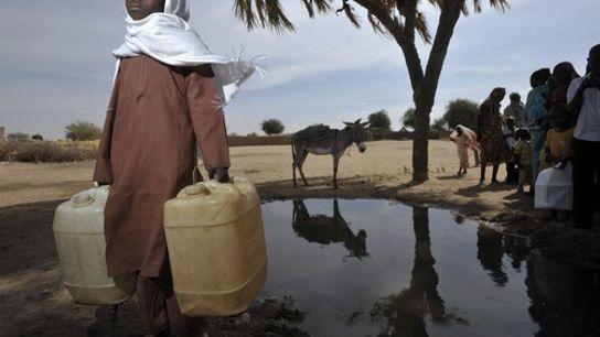 Un enfant repart du puits avec des bidons d'eau dans un camp de réfugiés à Nyala, ...