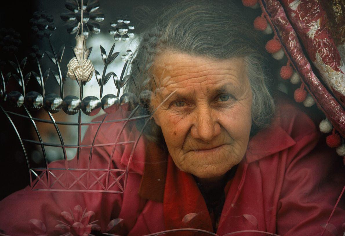 Angleterre, 1972 : une femme du voyage âgée jette un œil à travers de la vitre d'une ...