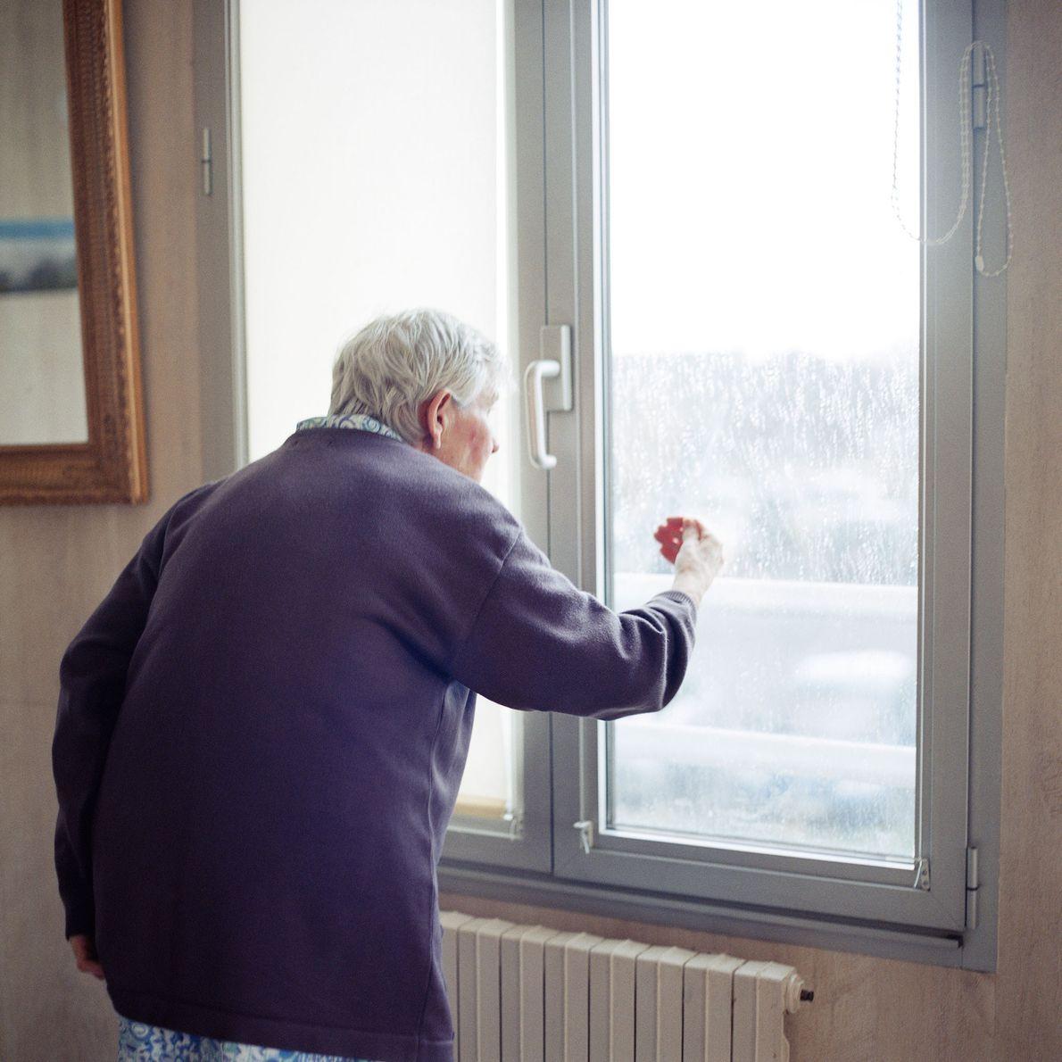 Une résidente regarde à travers une fenêtre verrouillée du département.