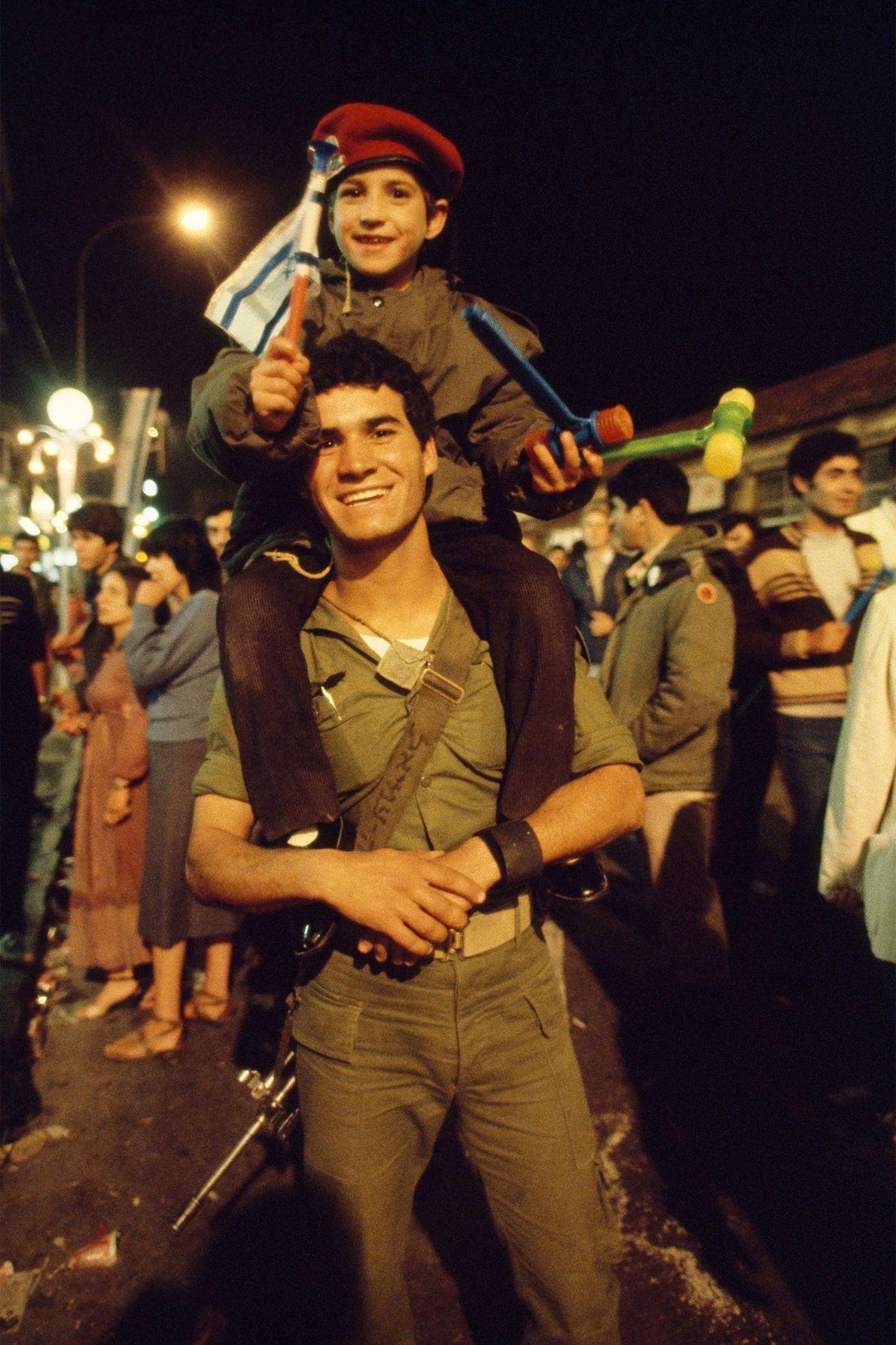 À Jérusalem, un fils agite le drapeau de l'Israël depuis les épaules de son père, un ...
