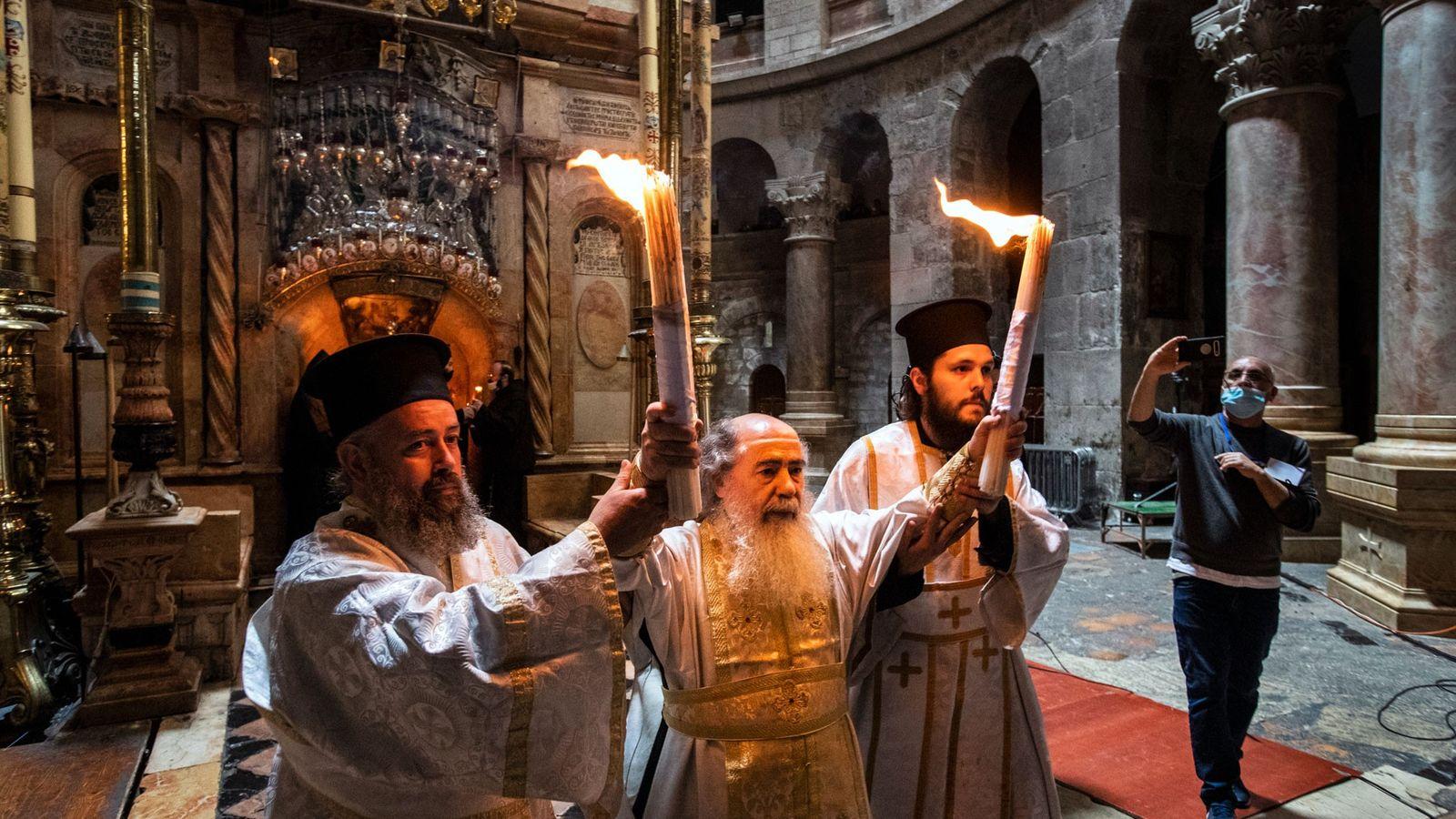 Deux prêtres aident le patriarche Théophile III à porter le Feu sacré à sa sortie de l'Édicule. ...