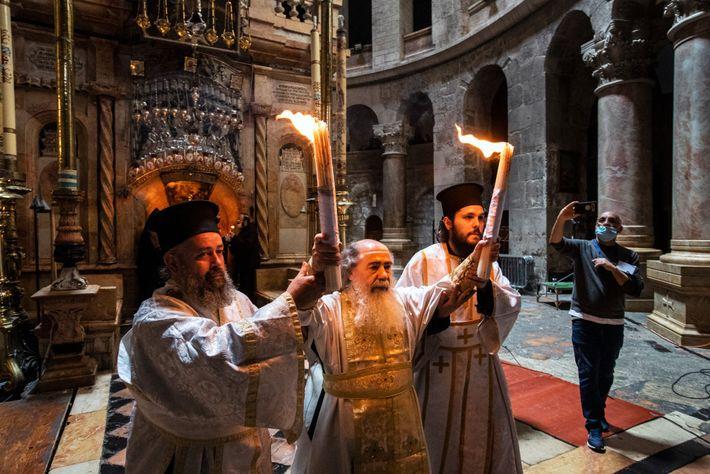 Deux prêtres aident le patriarche ThéophileIII à porter le Feu sacré à sa sortie de l'Édicule. ...