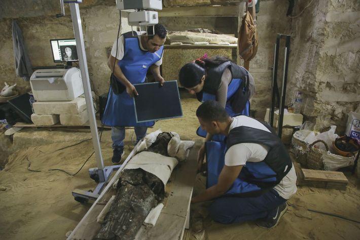 Sahar Saleem, spécialiste en paléoradiologie (ici entre deux techniciens), utilise une unité mobile de radiographie pour ...