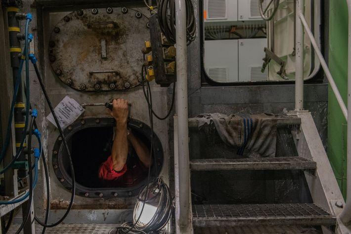 Un technicien de maintenance s'engouffre dans le réservoir à carburant du Polarstern. Le Polarstern est un ...