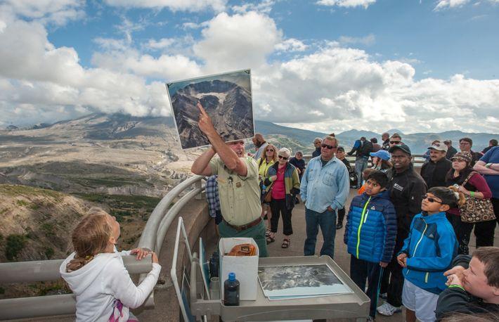 Un garde forestier brandit une photo où on peut voir les deux côtés est et ouest ...