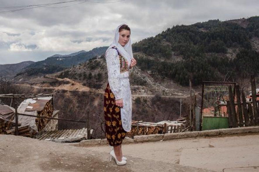 Vêtue d'une tenue traditionnelle, une jeune femme de Ribnovo est en route pour le mariage de Letve Osmanova et Refat Rvdikov.
