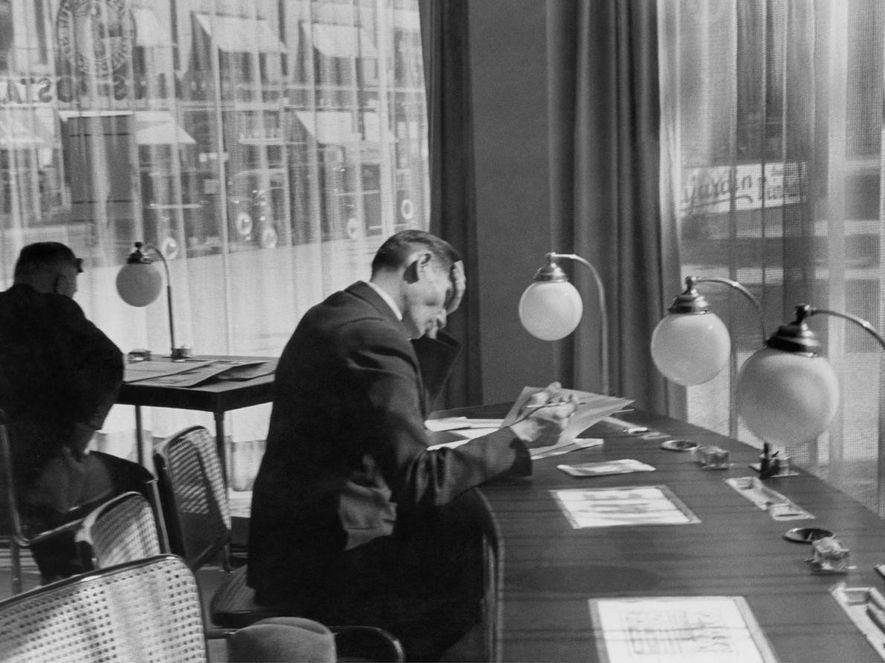 Un homme rédige une lettre dans un bureau de poste berlinois.