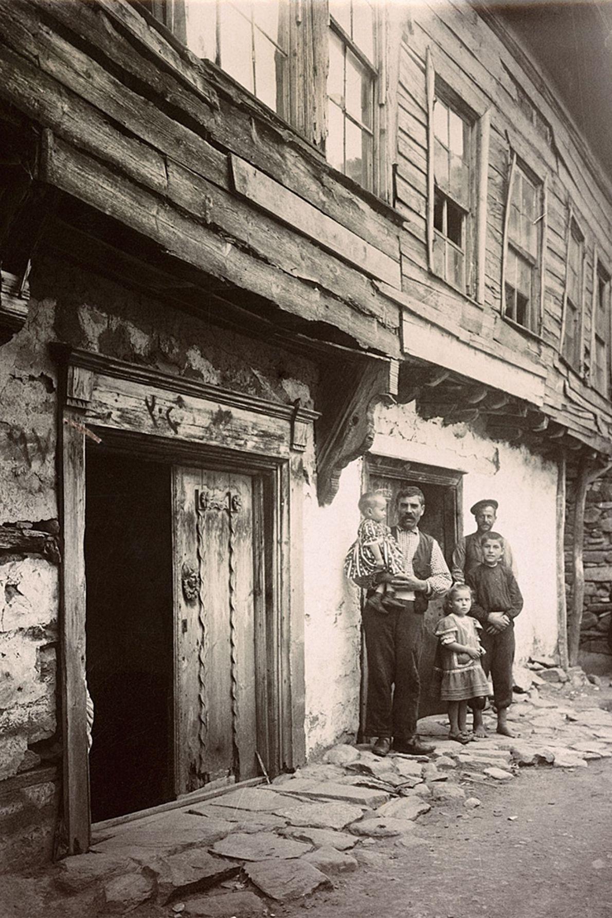 Une famille pose le long des bâtiments d'une ruelle pavée sur l'île turque de Marmara, située ...