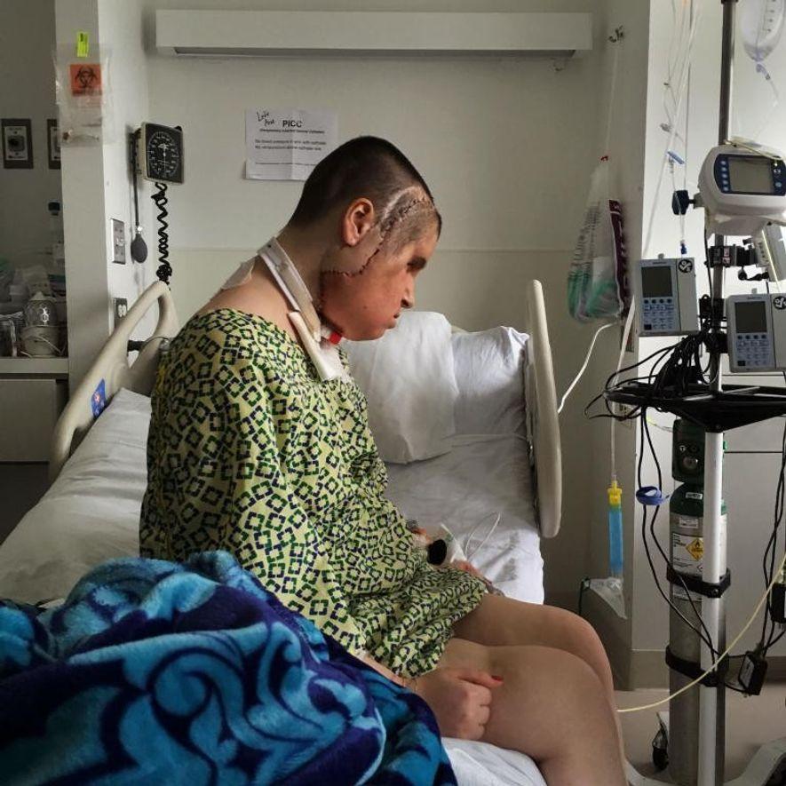 Katie prend un moment seule dans sa chambre, ce qui est rare à l'hôpital, car les médecins s'arrêtent souvent pour faire un point sur son état. Son nouveau visage, avec les sutures apparentes, était encore assez enflé.