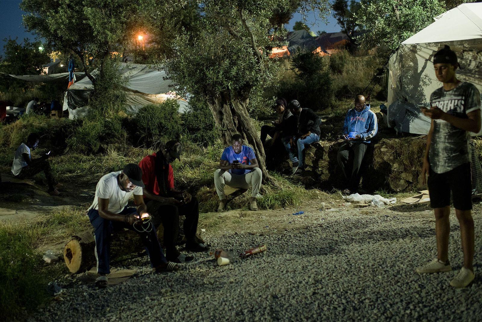 Des habitants du camp de fortune, surnommé l'Oliveraie, se rassemblent aux endroits où le réseau téléphonique ...