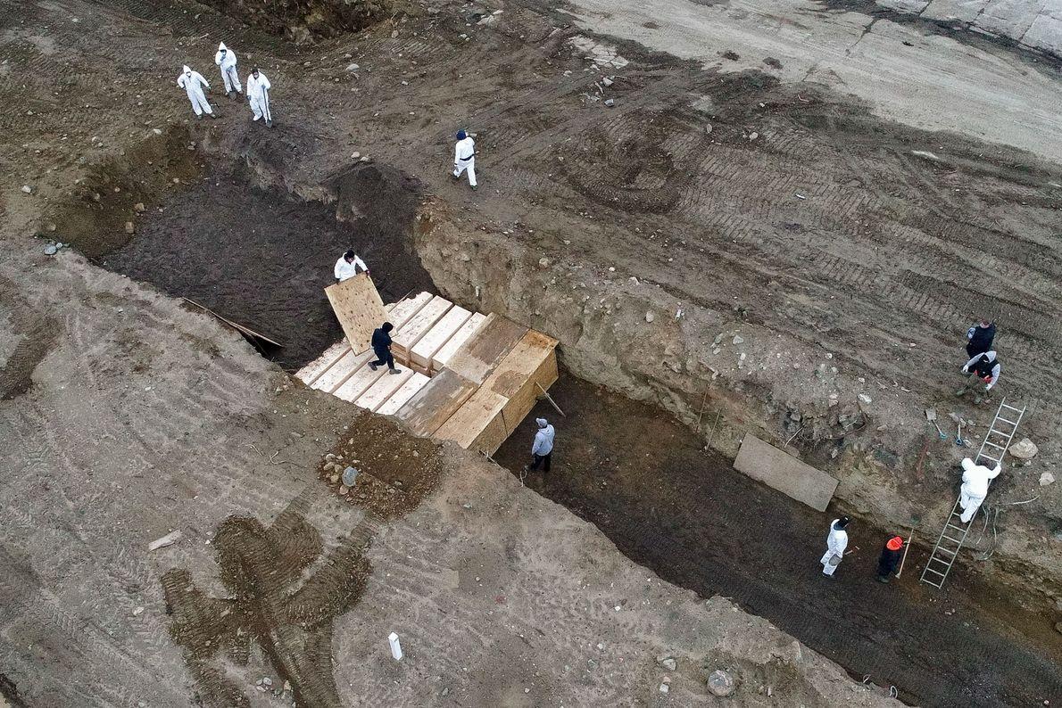 Des ouvriers vêtus de combinaisons de protection enterrent les défunts le 9 avril 2020, le jour où le ...
