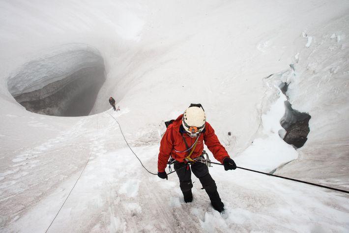 Neil Marchington, arpenteur et chercheur, descend en rappel vers le guide Jared Smith et l'entrée de ...