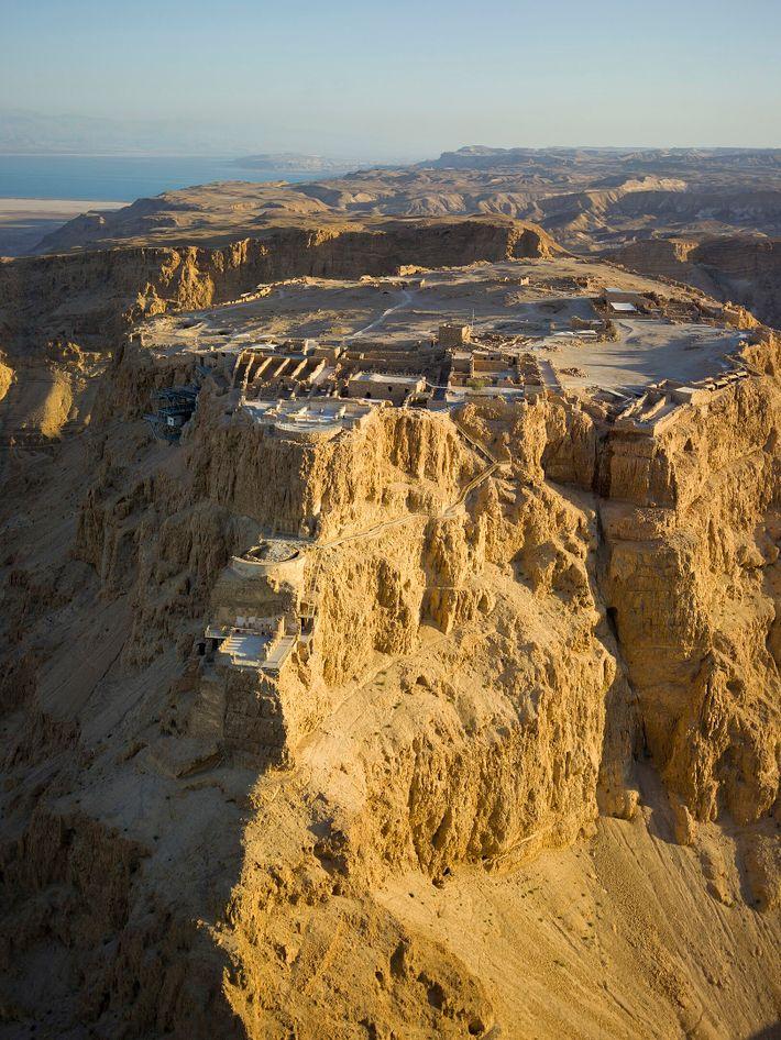 Vue aérienne sur les fortifications de Massada dans le désert de Judée, avec la mer Morte visible en arrière-plan.