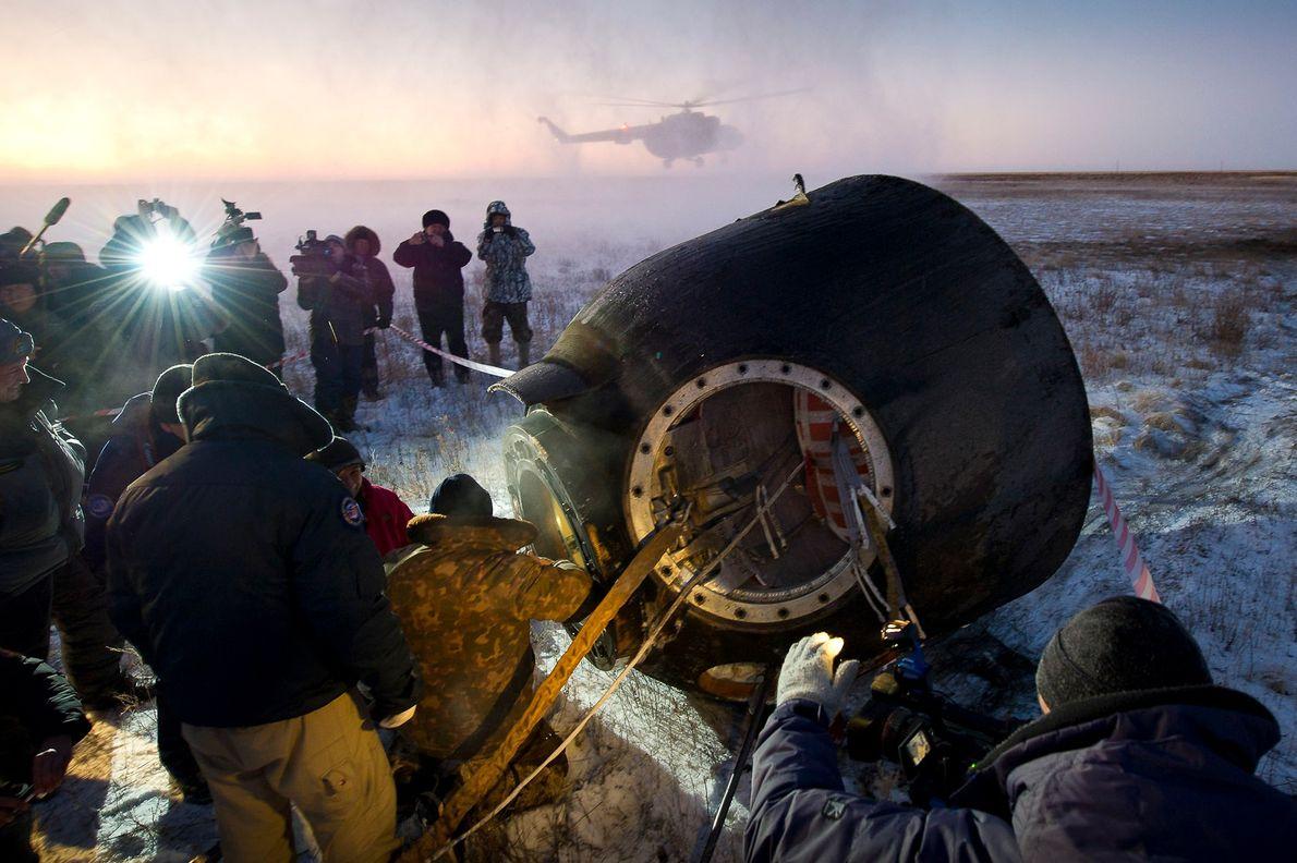 Le personnel de soutien aide les passagers de la fusée Soyouz TMA-02M, l'astronaute de la NASA ...