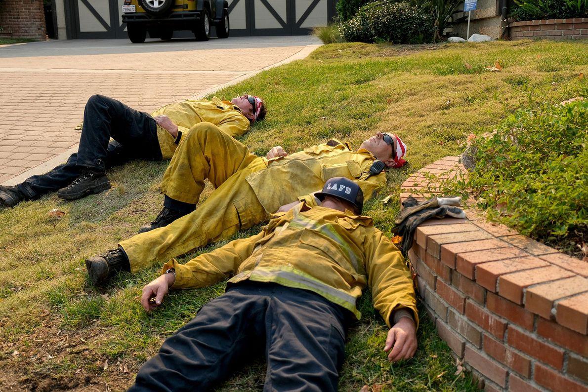 Après avoir lutté contre l'incendie Woolsey le vendredi 9 novembre, des pompiers, épuisés, se reposent au ...