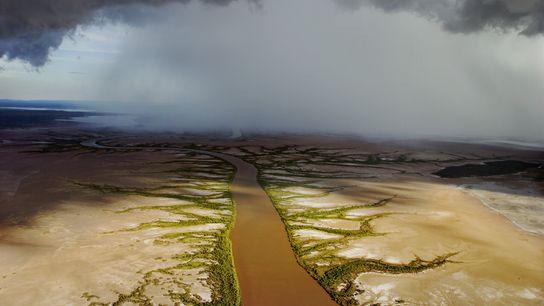 De lourds nuages chargés de pluie se forment au-dessus d'une rivière dans l'ouest de l'Australie.