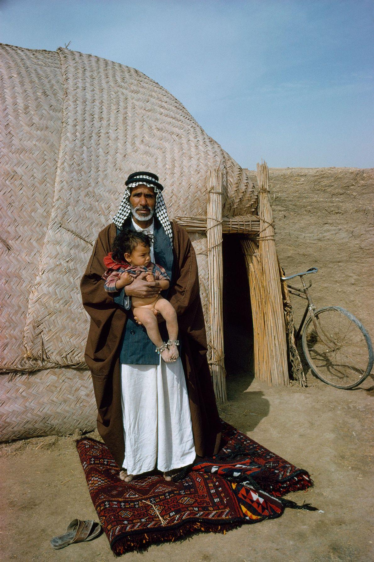 En Iraq, un père prend la pose sur un tapis devant sa hutte en joncs.