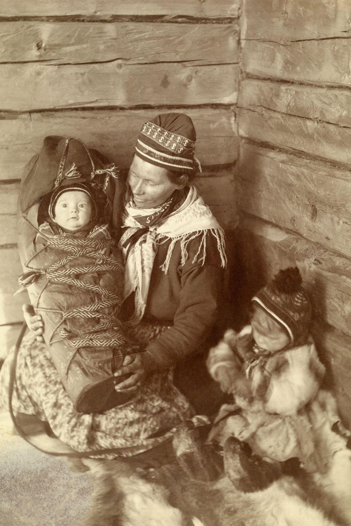 Une femme samie, un enfant en bas âge et un bébé s'assoient sur des peaux pour ...