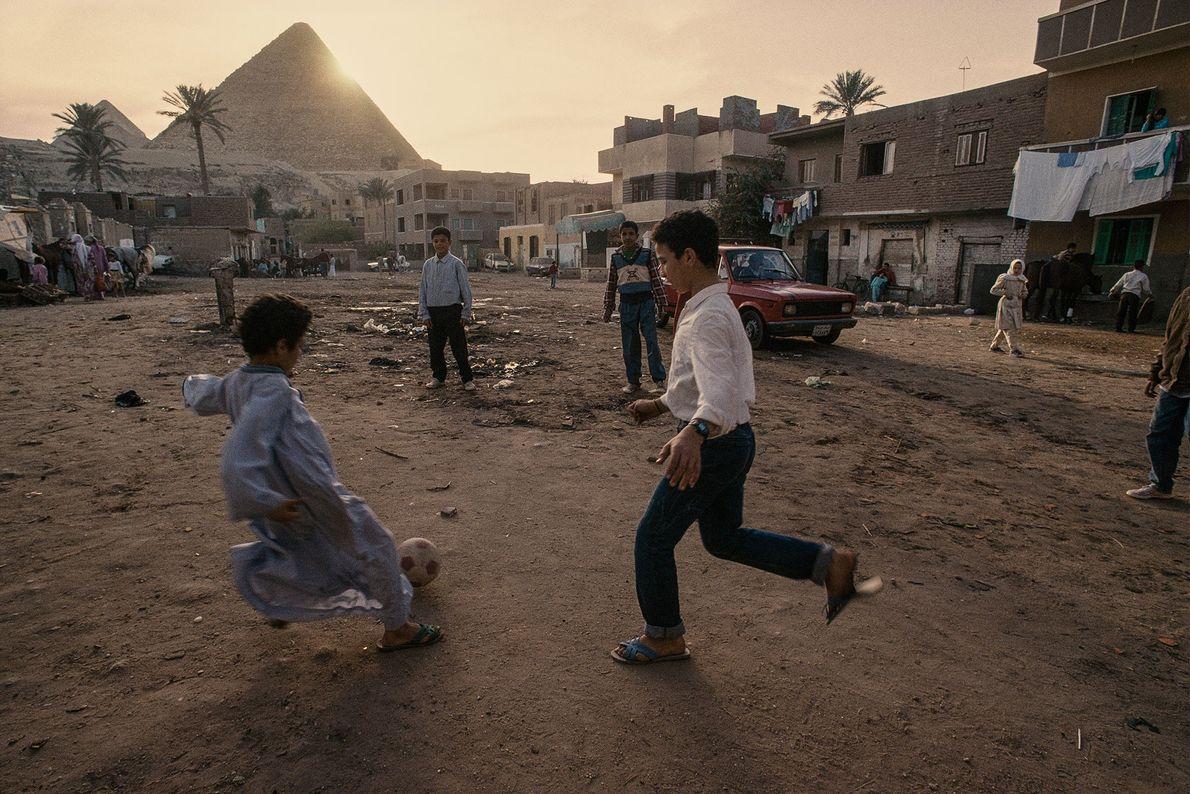 Les enfants d'un village jouent au football au pied des pyramides de Gizeh, en Égypte.