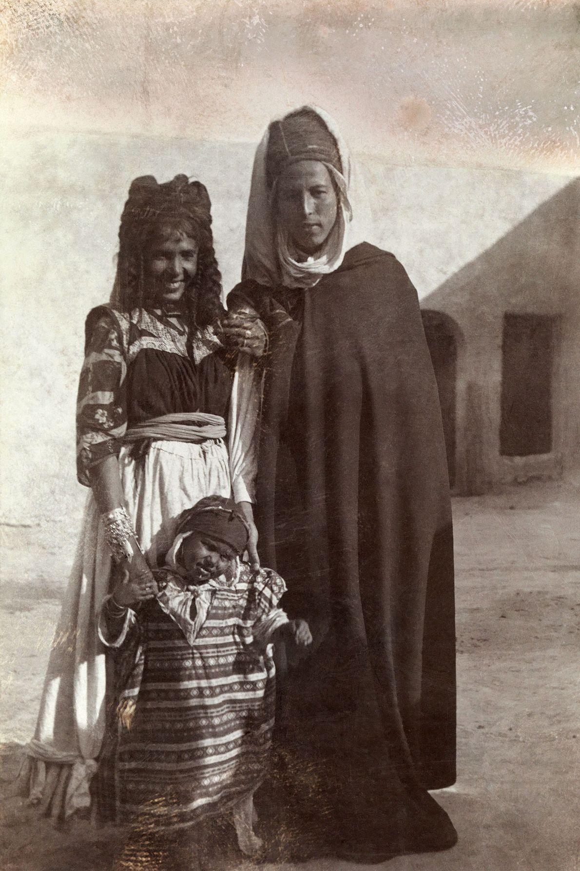 Au début des années 1900, un jeune couple d'Algériens posent avec leur enfant devant un bâtiment ...