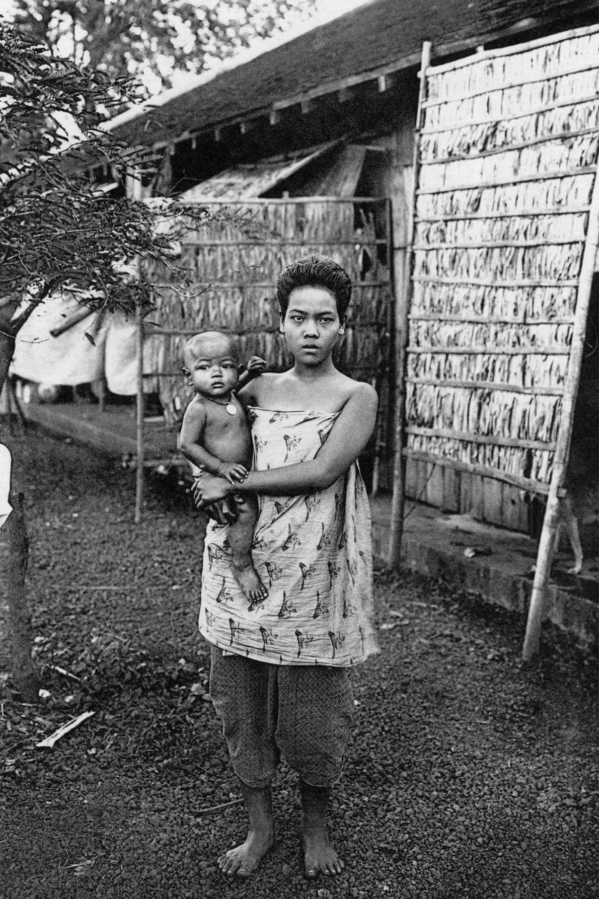 Une mère au Cambodge pose son enfant sur sa hanche.