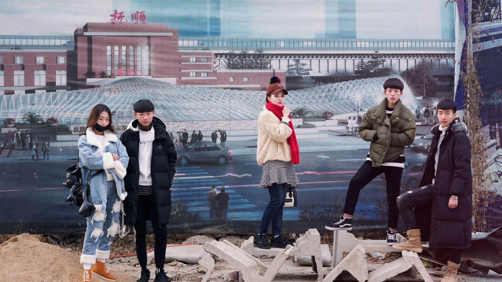 Des étudiants attendent avant de passer un examen d'art devant des affiches faisant la promotion de ...