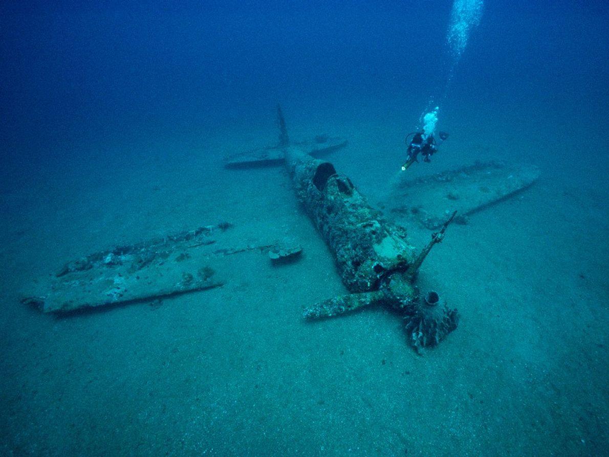 Un plongeur explore l'épave d'un avion de chasse japonais de la Seconde Guerre mondiale près de ...