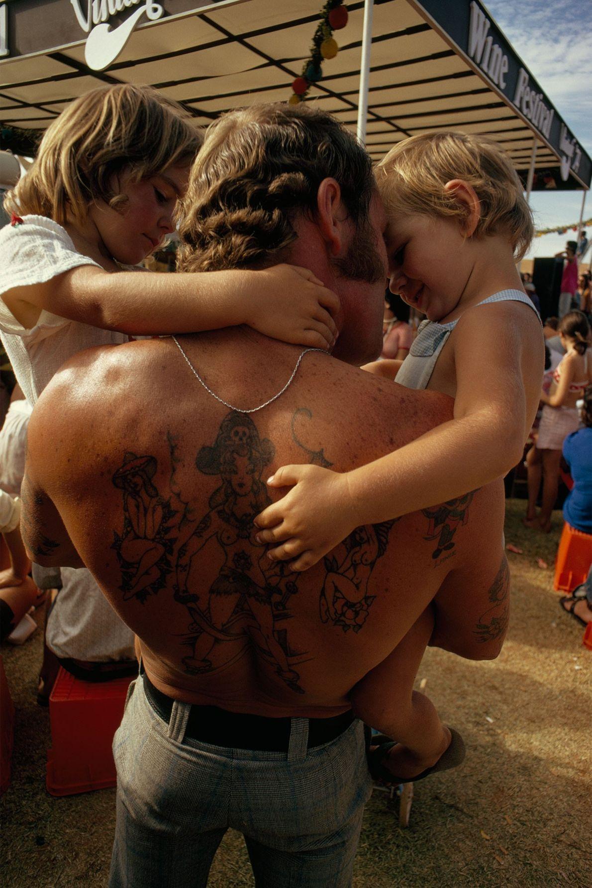 À Caversham en Australie, un père au dos tatoué porte ses deux enfants dans ses bras.