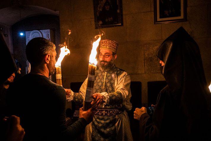 Le Père Révérend Sarukhanyan porte les cierges allumés par le Feu sacré au sein de l'église ...