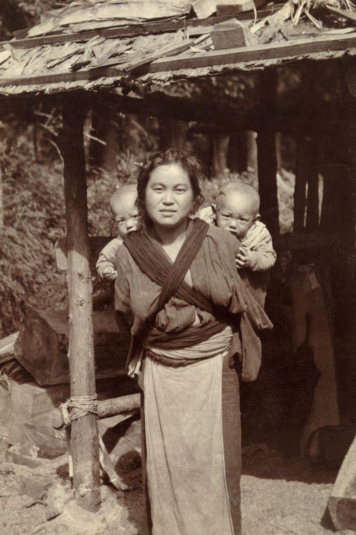 Une femme japonaise porte ses jumeaux sur son dos.