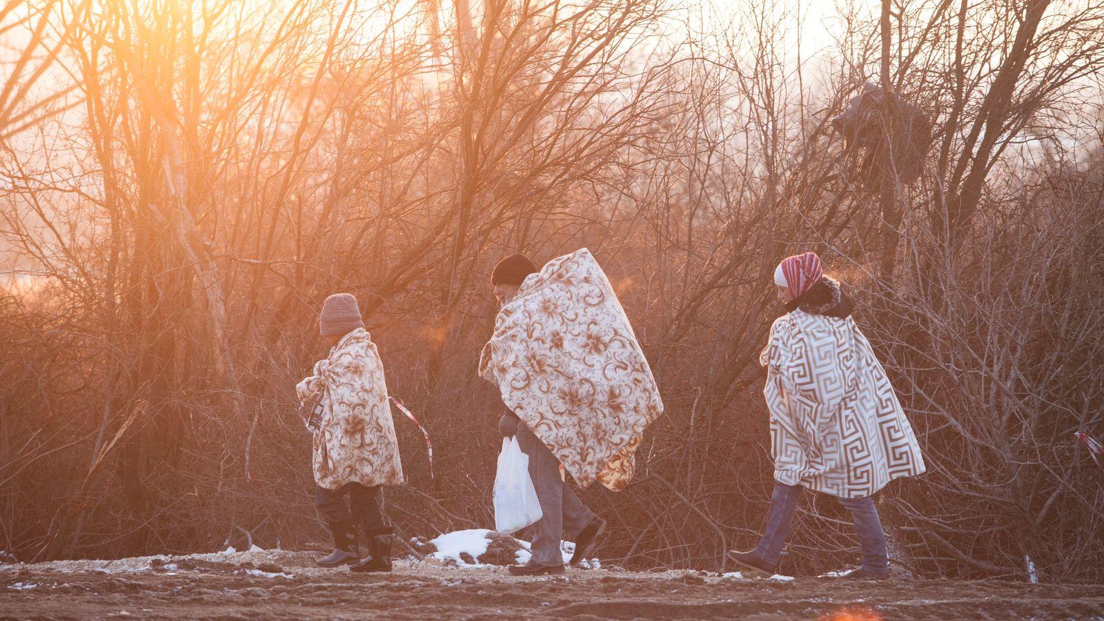 Des réfugiés enveloppés dans des couvertures et des vêtements d'hiver pour tenter de se réchauffer contre ...