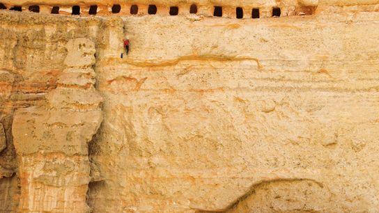 Un grimpeur agile escalade une paroi fragile