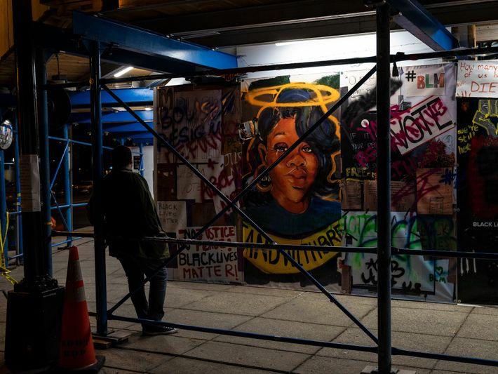 La veille de la marche « Commitment March », un piéton s'arrête en face d'une peinture murale représentant Breonna Taylor, ...