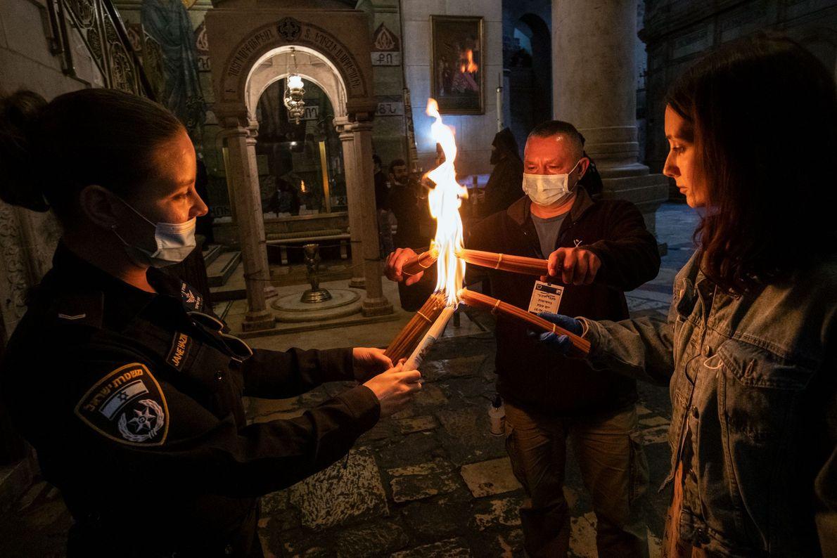 Une officière de la police de Jérusalem partage le Feu sacré avec certains participants à la ...