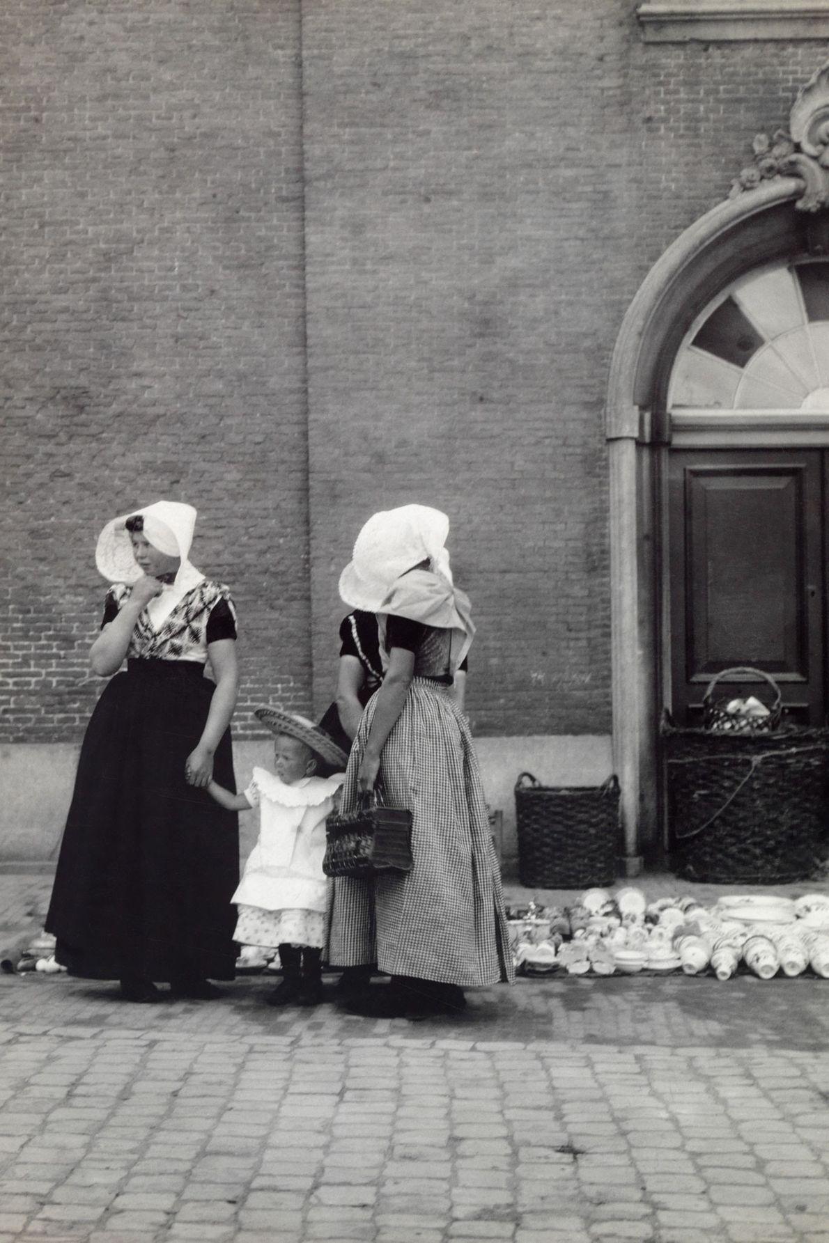Une servante et sa supérieure tiennent les mains d'un enfant en faisant des emplettes en Hollande.