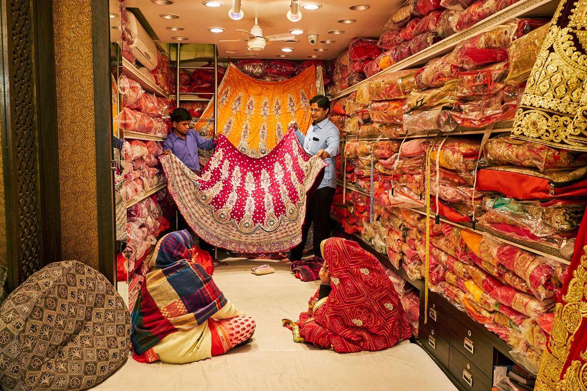 Des femmes achètent des saris empilés du sol au plafond dans un magasin de Jaipur. Les achats ...