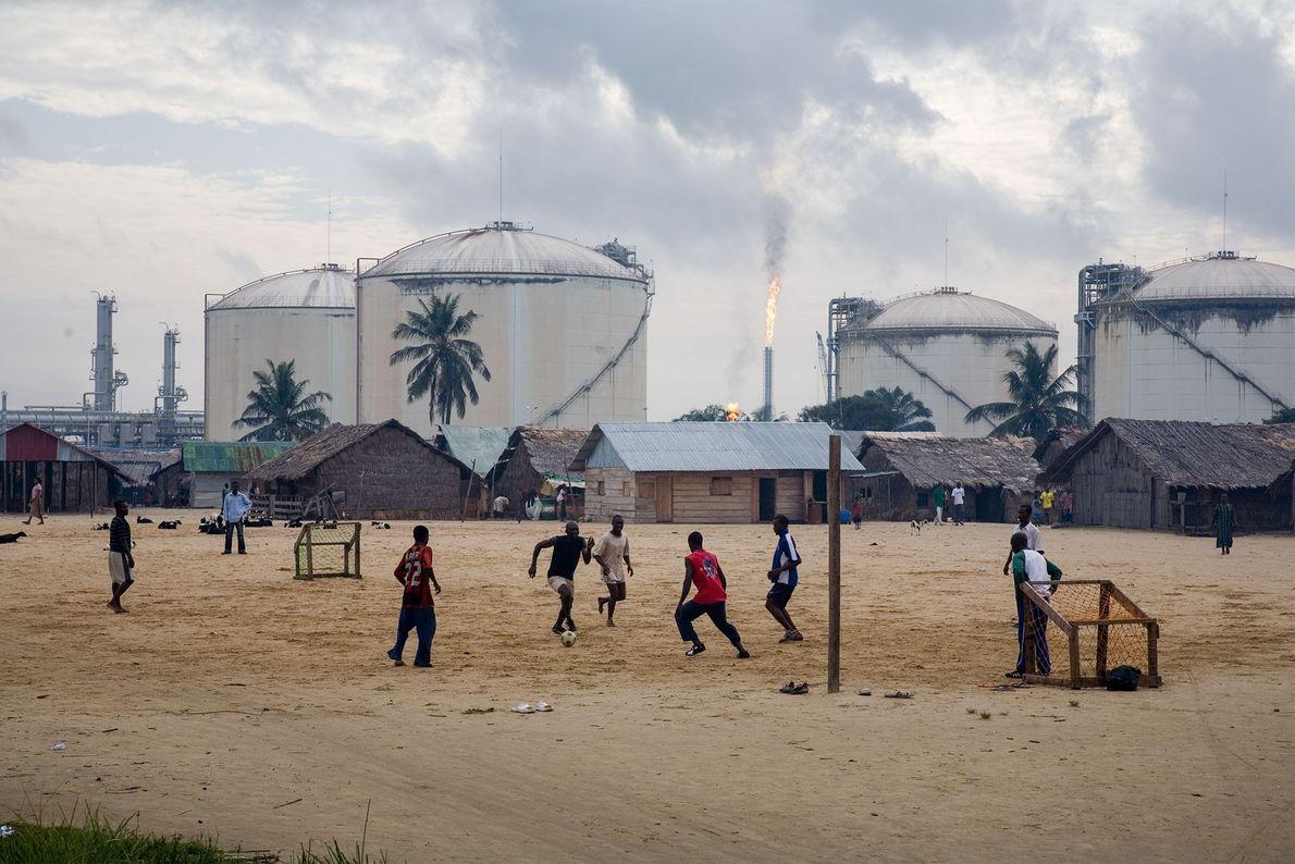 Au Nigeria, sur l'île Bonny, des adolescents jouent au football à côté des réservoirs de stockage ...