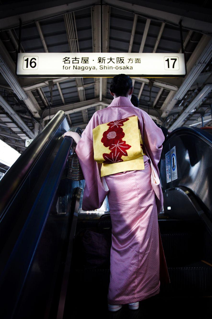 Une femme en kimono s'apprête à monter à bord d'un Shinkansen, un train à grande vitesse. ...