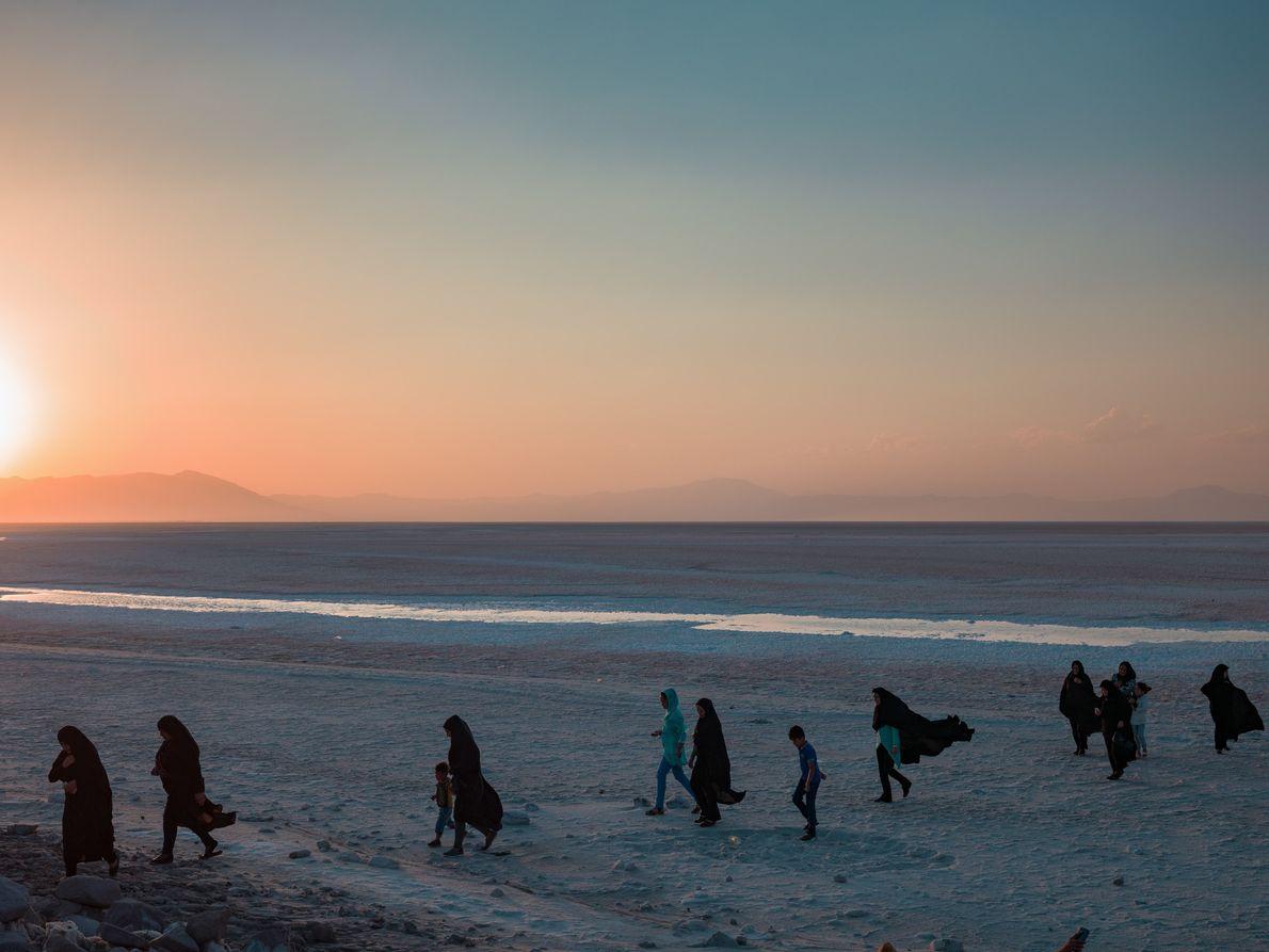 Une famille se promène sur la plage alors que le soleil se couche au-dessus du lac ...