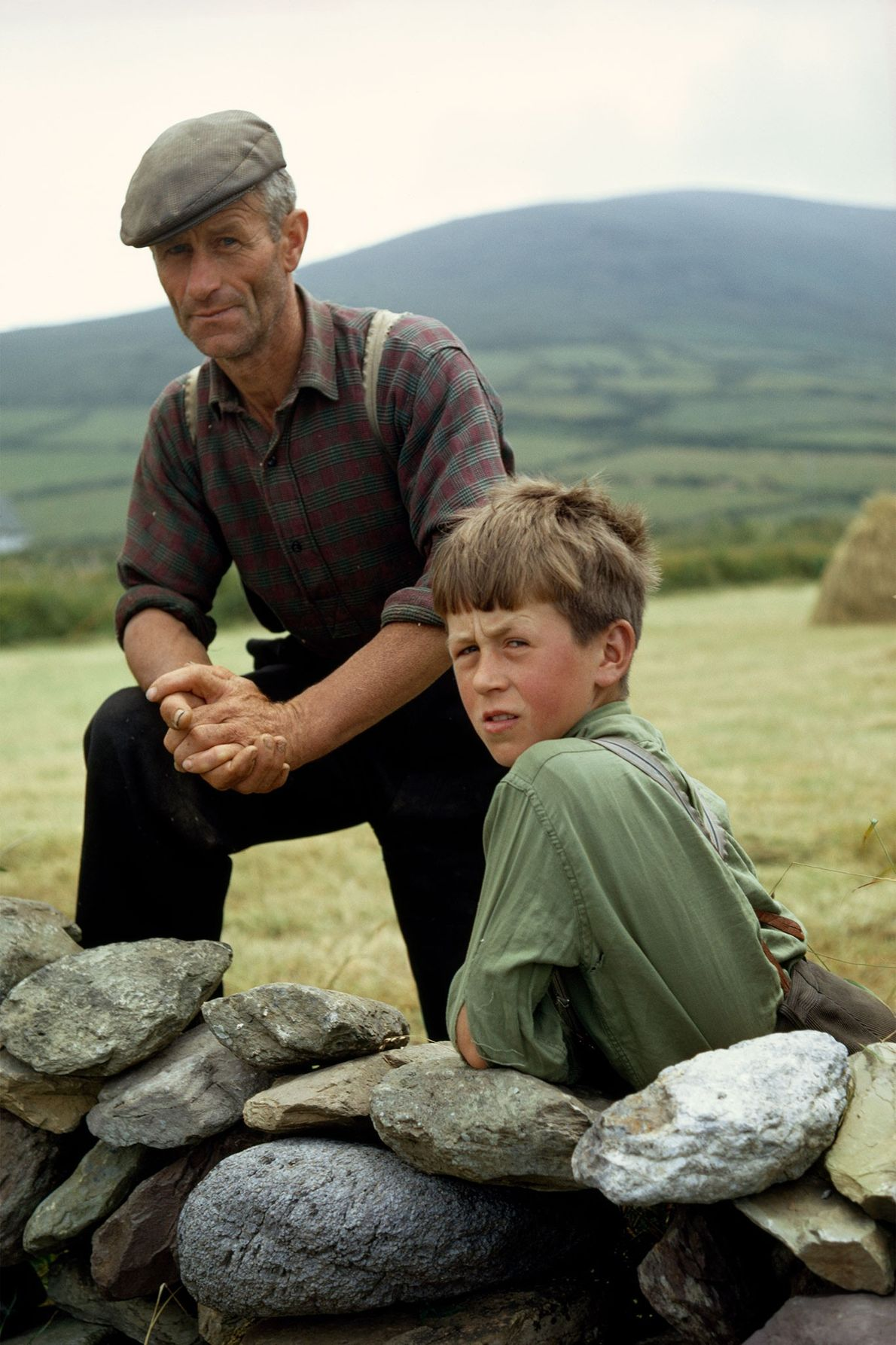 Un agriculteur irlandais et son fils posent appuyés contre un mur de pierres dans la péninsule ...