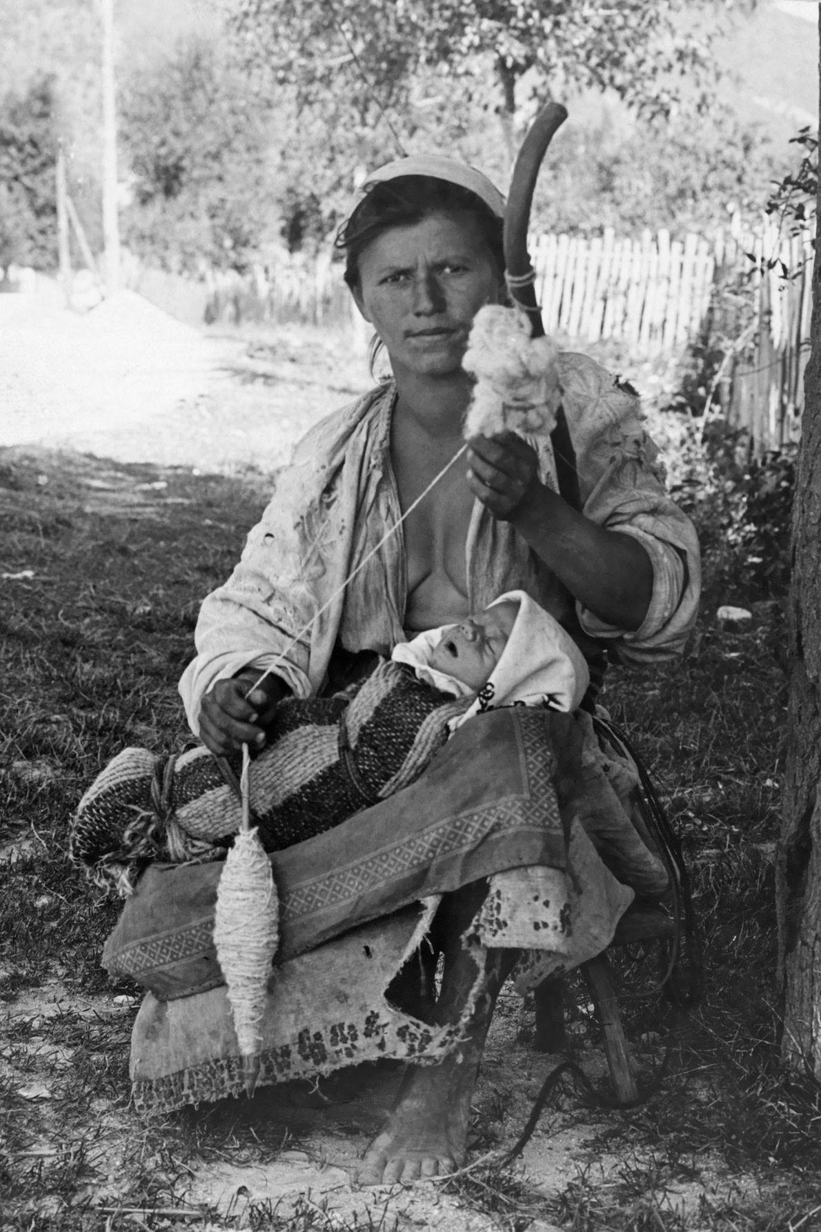 Une femme hongroise tisse de la laine pendant que son bébé dort sur ses genoux.