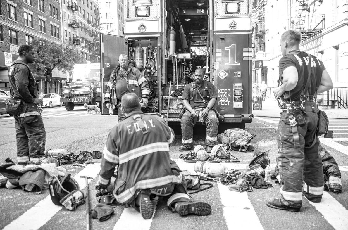 Les pompiers de New York se reposent quelques instants après avoir maîtrisé un incendie dans le ...
