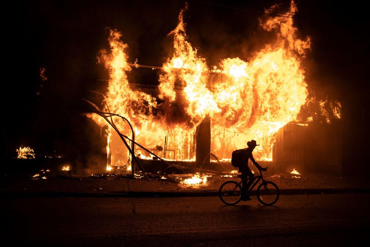 Un manifestant passe devant un bâtiment en flammes lors des manifestations en cours, suite au décès ...