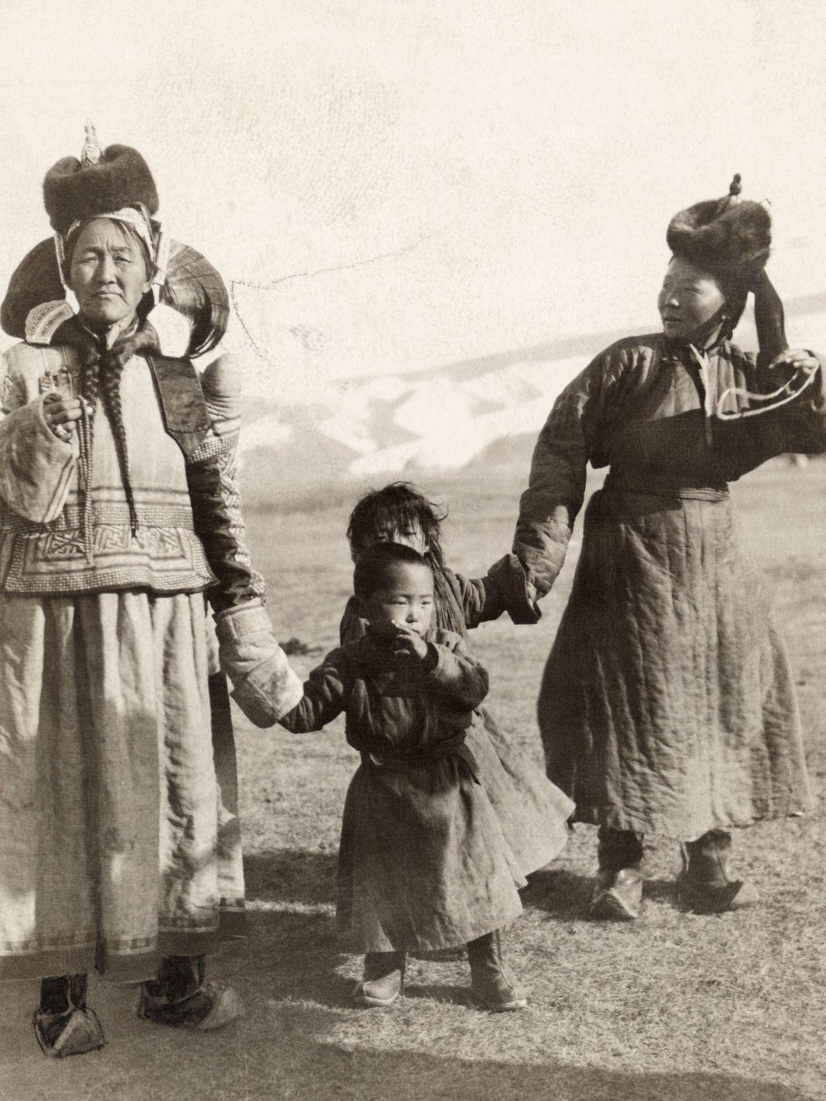 Des femmes marchent main dans la main avec leurs enfants dans le nord de la Mongolie.