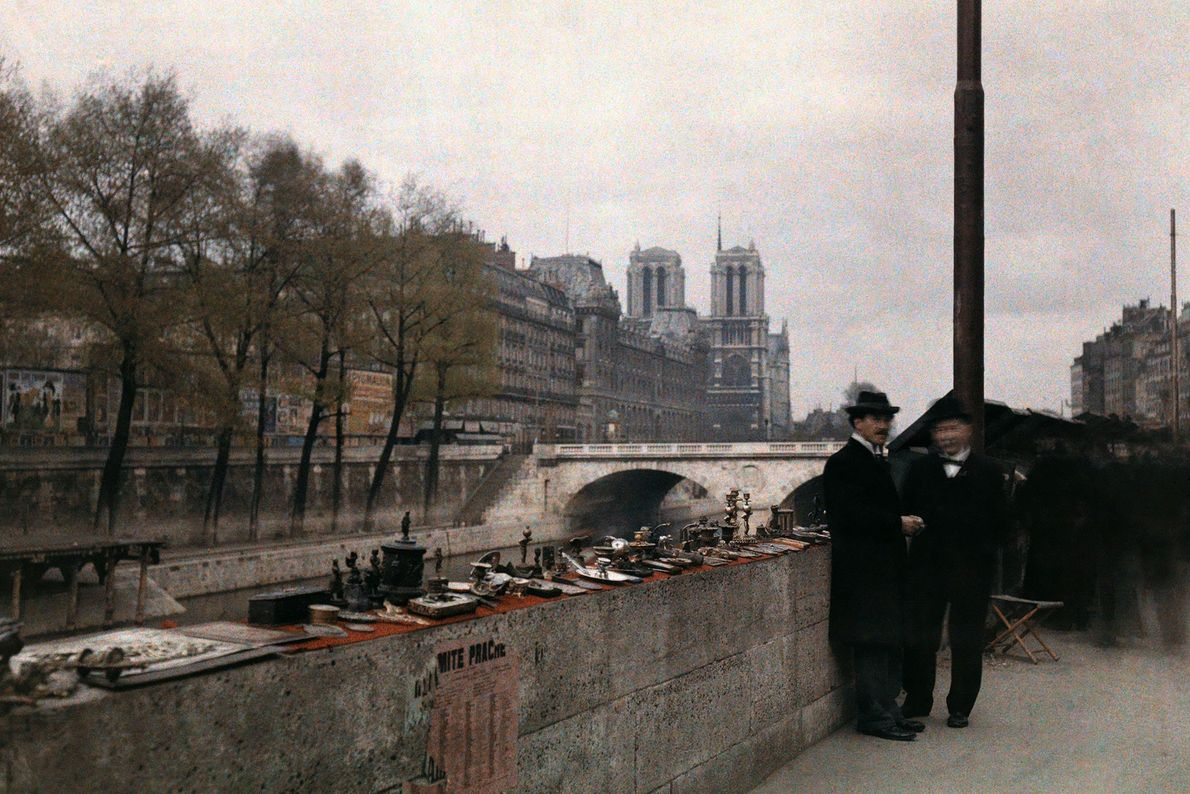 Deux hommes se tiennent à côté de bibelots en vente sur les bords de Seine dans ...